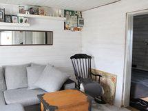 Huoneen nurkassa sijaitsee nimittäin vanha pyöreä takka, joka luo kotiin tunnelmaa ja kodikkuutta.
