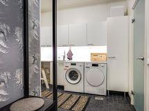 Kodinhoitohuoneessa runsaat määrät kaapistoja muun muassa pyyhkeille ja liinavaatteille.