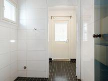 Vaalea kylpyhuone , jonka vieressä kodinhoitotila