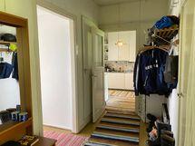 Tilava eteinen. Oikealla on saunan pesuhuoneen ovi.
