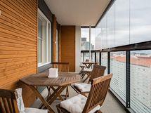 Asunnon tilava lasitettu parveke. Yleisilmettä pehmentää puupanetoitu pääty- ja taustaseinä