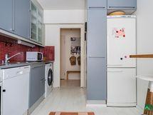 Oikealla jääkaapi/pakastin yhdistelmän vieressä on apteekkarinkaappi.