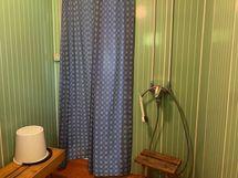 Tilavassa pesuhuoneessa suihku. Suihkuverho suojaa ovea vesiroiskeilta.