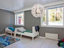Makuuhuoneen hillitty värimaailma.