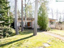 Suuri talo kätkeytyy puiden katveeseen