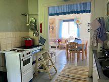 Keittiöstä olohuoneeseen on leveä aukko. Vasemmalla liesi ja puuhella