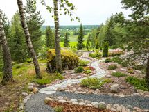 Kivipuutarhan keskellä kulkee osittain murskepintainen, osittain liuskekivillä päällystetty polku.